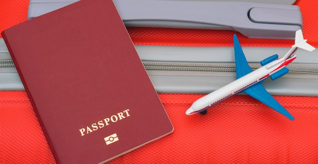The red passport and model of the plane lie on the red suitcase. Premium Photo