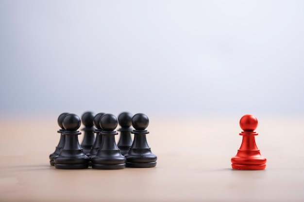 Red pawn chess stepped out of group to show different thinking ideas and leadership. business technology change and disruption for new normal concept. Premium Photo