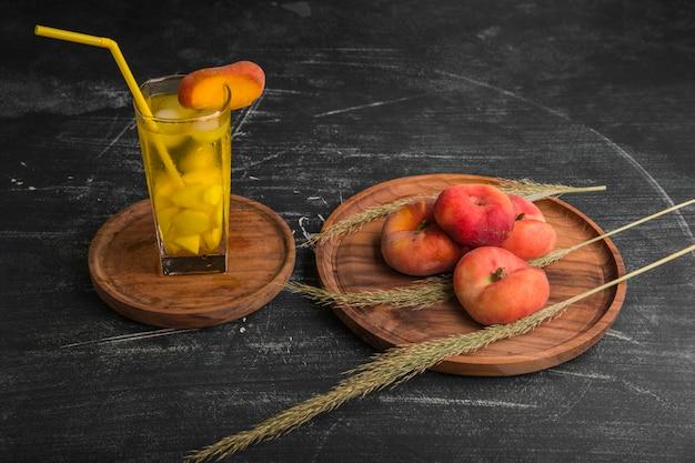 Pesche rosse con un bicchiere di succo in un piatto di legno Foto Gratuite