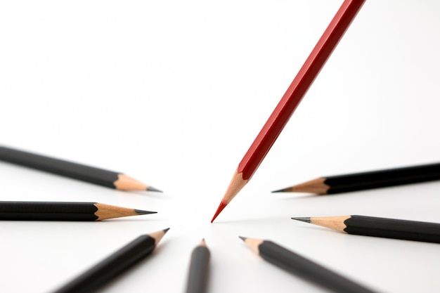 Red pencil standing out from crowd of plenty identical black fellows on white table. Premium Photo