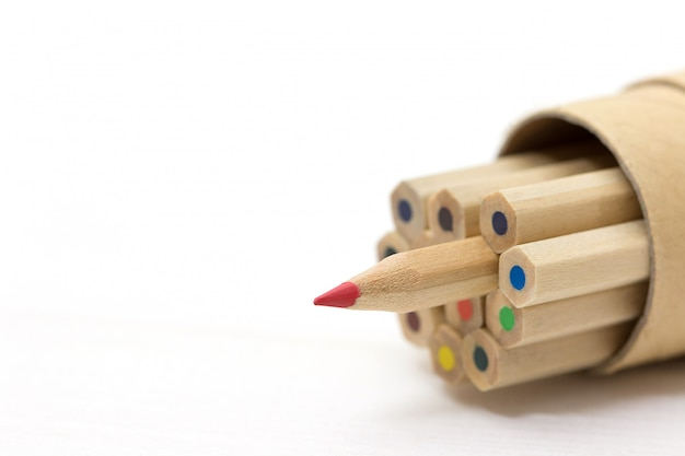 Red pencil standing out from crowd on white table. Premium Photo