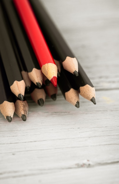 Red pencil stands out from the crowd of black pencil on a wooden white background. Free Photo