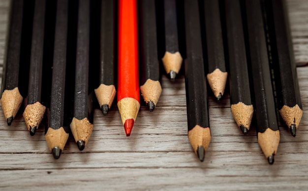 La matita rossa si distingue dalla massa della matita nera su uno sfondo bianco di legno. Foto Gratuite