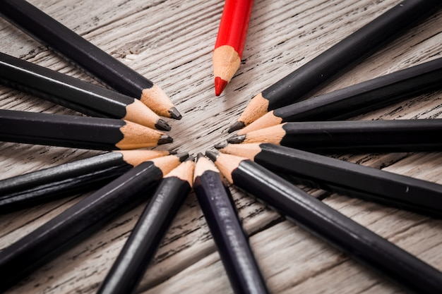 Red pencil stands out from the crowd of black  on a wooden white background. Premium Photo