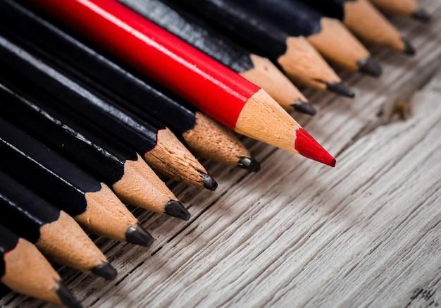 La matita rossa si distingue dalla massa del nero su un tavolo di legno bianco Foto Gratuite