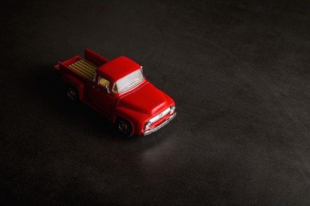 Red pickup model on the black floor Free Photo