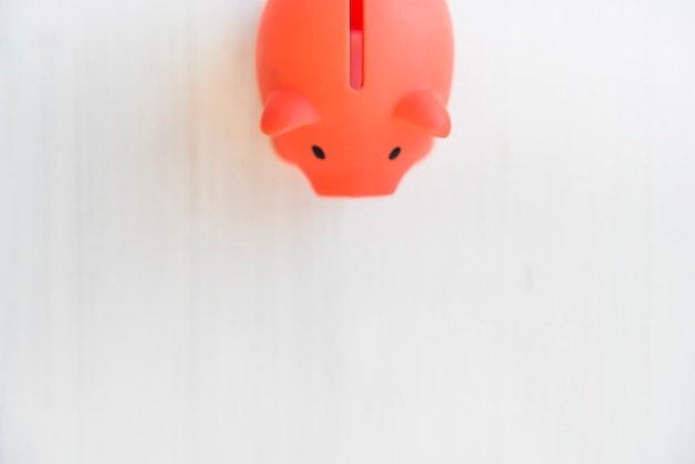 Red piggy bank on white table Free Photo