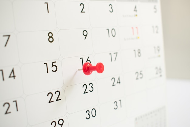 A red pin on the event calendar.background, close up, time Premium Photo