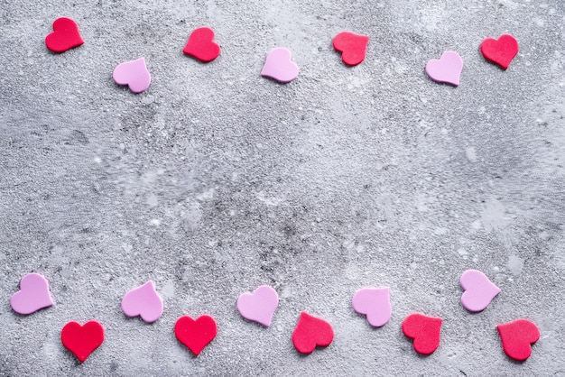 Red and pink hearts on the stone background. valentine's background for postcard Premium Photo
