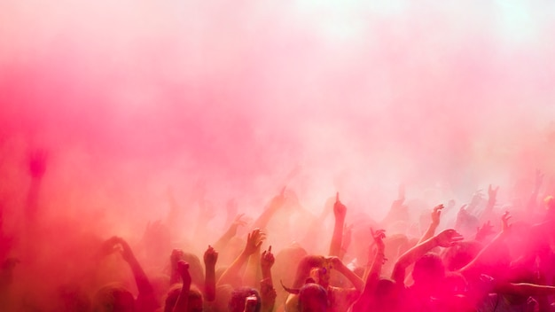 Red and pink holi colors over the crowd Free Photo