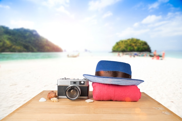Red pink tower, blue hat, old vintage camera and shells over wooden floor on sunshine blue sky and ocean background Free Photo