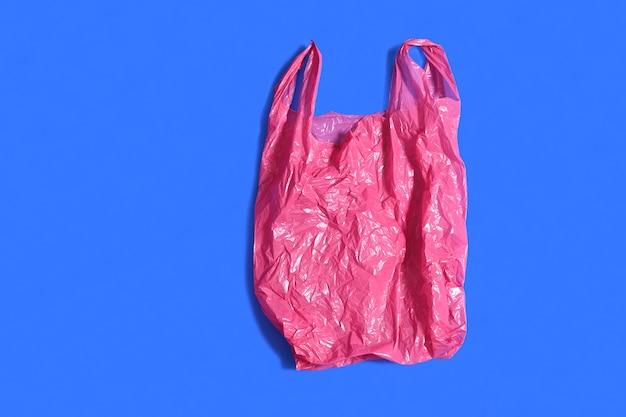 青色の背景に赤いビニール袋 Premium写真