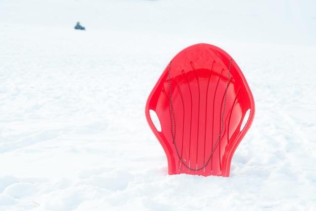 赤いプラスチック製のそり、そり、屋外の白い雪の背景にそり。 Premium写真