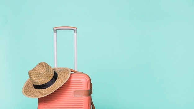Red plastic suitcase with hat Free Photo