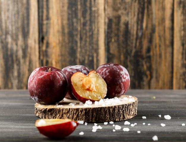 木製と灰色の表面、側面図に木製の部分に塩と赤い梅。 無料写真
