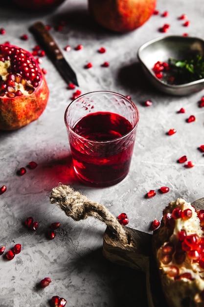 Красный гранатовый сок в стакане, спелый и разрезанный гранат и веточка мяты на сером фоне бетона. концепция витаминов, антиоксидантов и здорового питания. заложить квартиру. вид сверху. Premium Фотографии