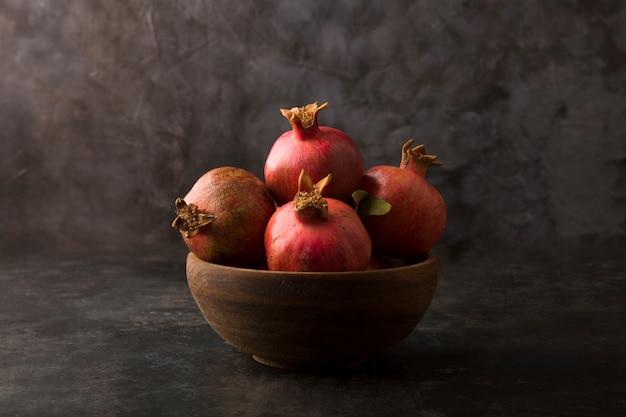 Красные гранаты на деревянном блюде на мраморе Бесплатные Фотографии