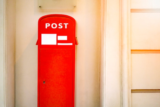 A red post box near the wall in city Premium Photo