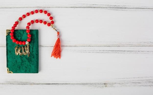 白い机の上の緑のカバーイスラム教の神聖な本kuranに赤の祈りビーズ Premium写真
