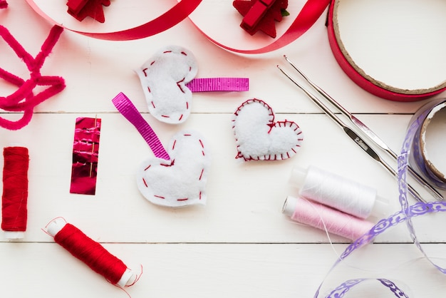 Red and purple ribbon; spools; crochet needle and heart shape on white plank Free Photo