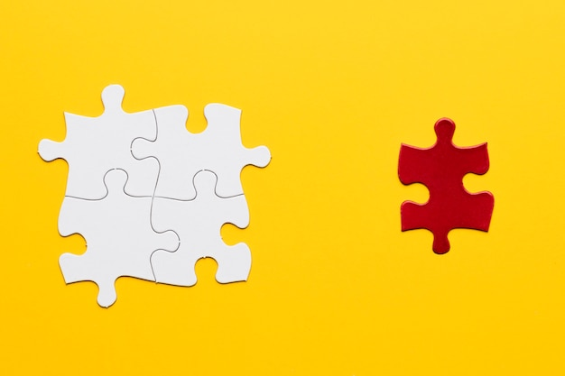 Red puzzle piece standing separately from white puzzle piece on yellow backdrop Free Photo