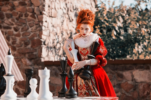 The red queen is playing chess. red-haired woman in a chic vintage dress. Premium Photo