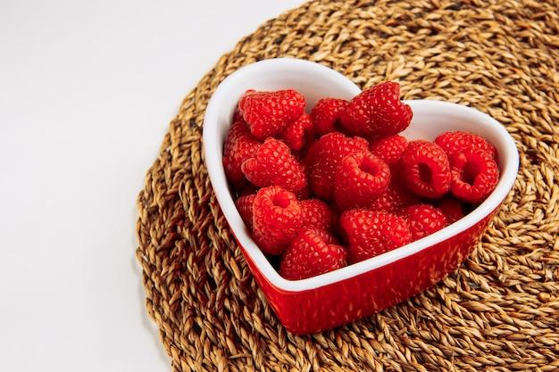 Lamponi rossi in un piatto a forma di cuore veduta dall'alto su una tovaglietta di vimini e sfondo bianco Foto Gratuite