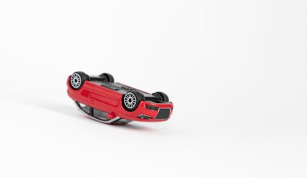 赤いガラガラおもちゃの車、事故の結果屋根に転倒。 Premium写真
