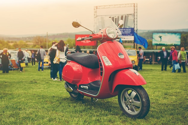Red retro scooter on grass Free Photo