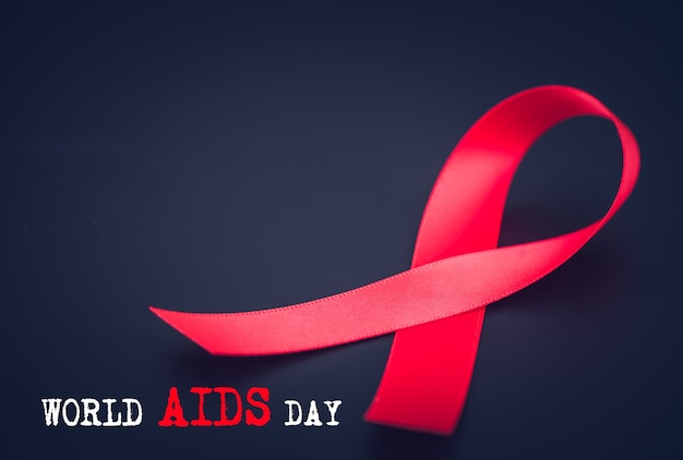 Red ribbon awareness on black background  for world aids day campaign Premium Photo