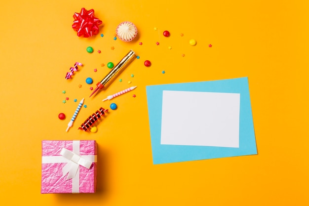 Red ribbon bow; aalaw; gems; streamers and sprinkles with greeting card and pink box on yellow backdrop Free Photo