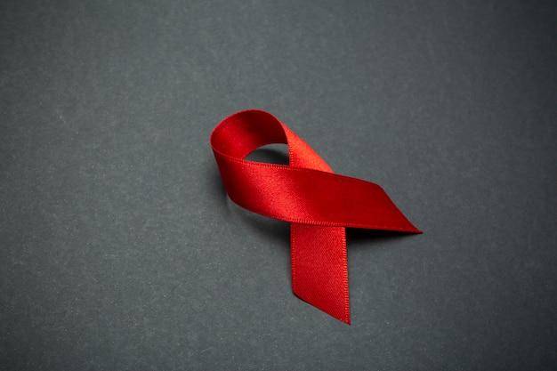 Красная лента на темно-сером фоне. символ всемирного дня борьбы со спидом или месяца осведомленности о раке или вич и концепции здравоохранения. копировать пространство Premium Фотографии
