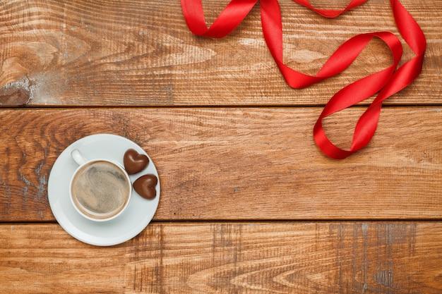 Il nastro rosso, piccoli cuori su fondo in legno con una tazza di caffè Foto Gratuite