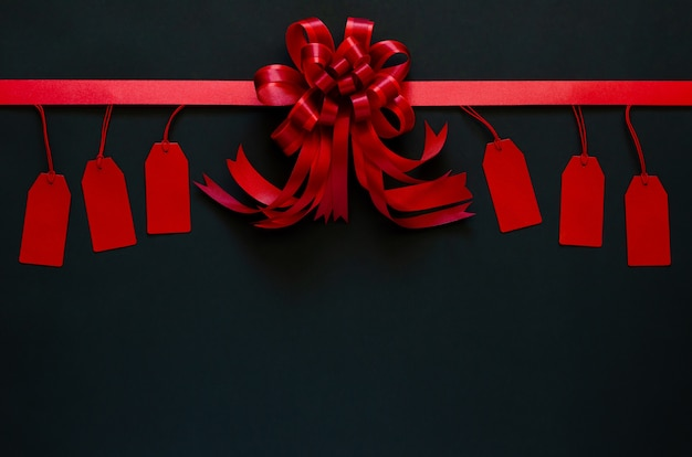 Красная лента с бантом и ценниками на черном. Premium Фотографии