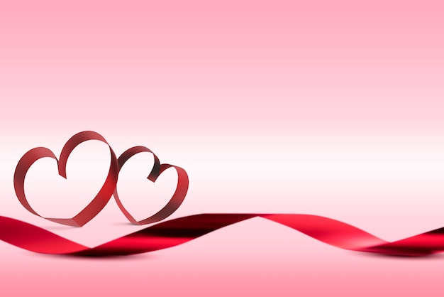 Red ribbons with ribbons shaped as hearts over pink background Premium Photo