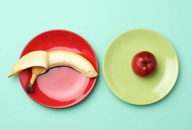 Красное спелое яблоко и банан лежат на круглой керамической тарелке Premium Фотографии