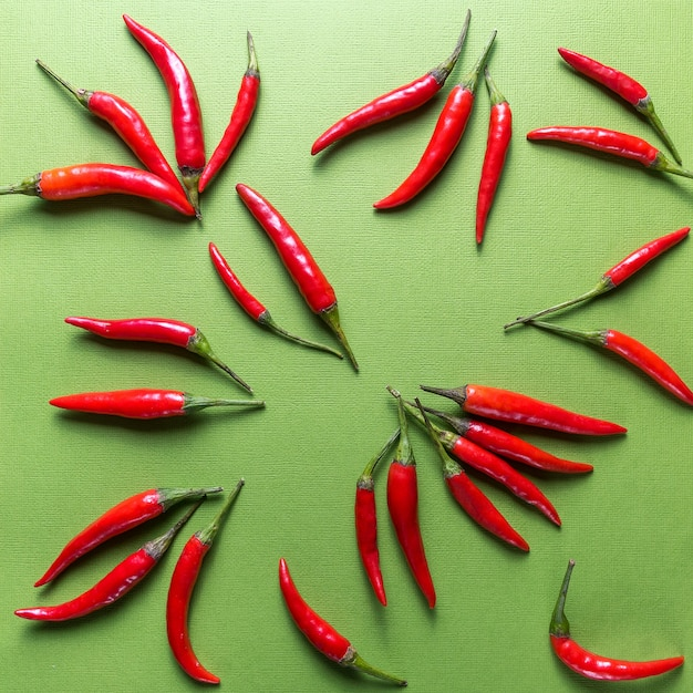 Red ripe small chili peppers pattern over green  in flat lay. Premium Photo