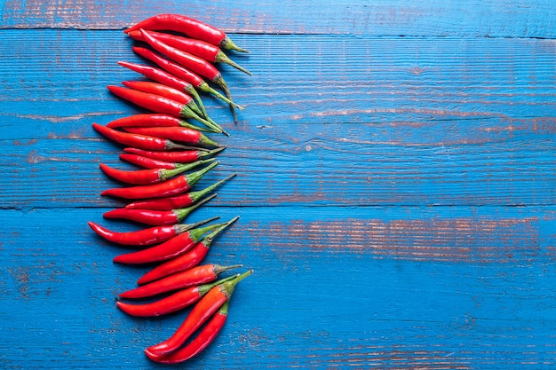 Red ripe small chili peppers pattern over old wooden blue background in flat lay. Premium Photo