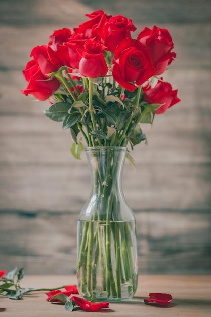 赤いバラの花束と花瓶と花びら Premium写真