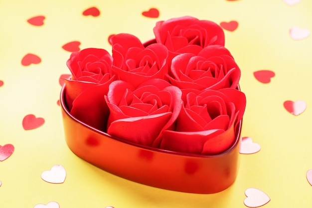 Red rose flowers in the shape of a heart on a yellow background.he concept of valentine's day, weddi