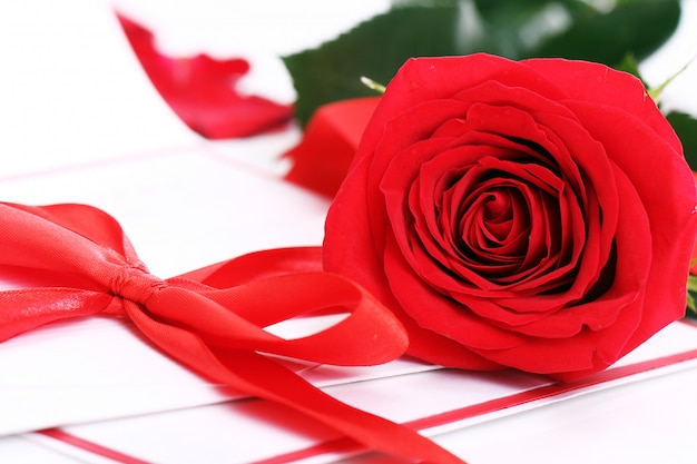 Red rose and holiday envelope Free Photo