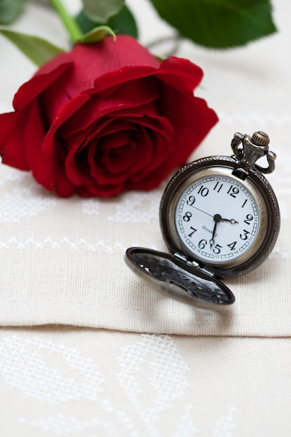 Red rose and pocket watch on napkin embroidered with cross Premium Photo