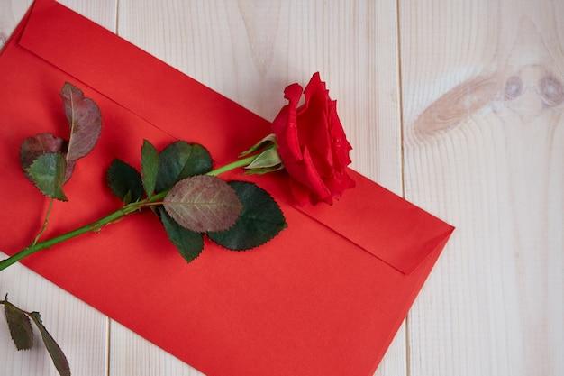 軽い木製の背景に赤いバラ、赤い封筒 Premium写真