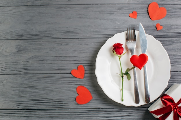 Red rose with cutlery on plate Free Photo