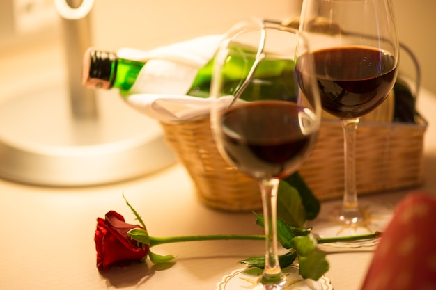Red rose with two glasses of wine Free Photo
