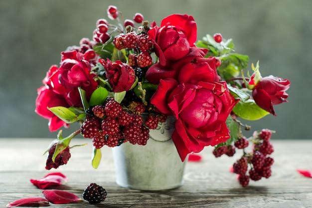 Красные розы и малина в вазе Premium Фотографии