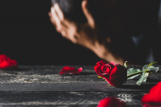 Red roses on a black table top with men who are stressed. Premium Photo