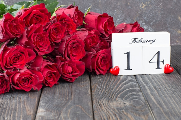 Red roses, red hearts and a calendar date of february 14 Premium Photo