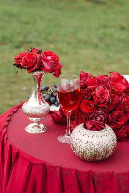 Red roses in a vase and on the table and a glass of red wine on the table, romantic decor Premium Photo