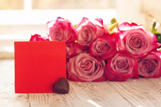 Red roses with blank red greeting card with heart chocolate for valentines day Premium Photo